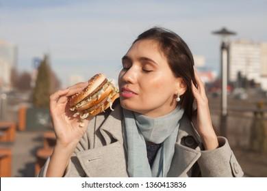 Beautiful girl is eating a cheeseburger