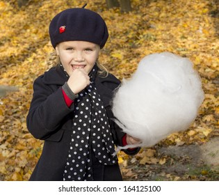 beautiful girl eating cotton candy at the autumn park