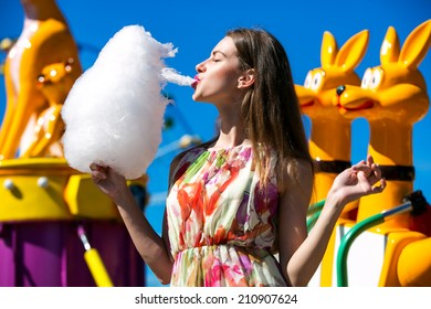 Beautiful girl eating cotton candy at an amusement park