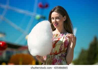 Beautiful girl eating cotton candy at an amusement park