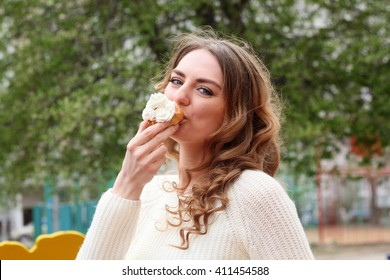 Beautiful girl eating a delicious cake with whipped cream and enjoy a delicious meal on the street