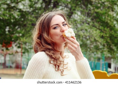 Beautiful girl eating a delicious cake with whipped cream and enjoy a delicious meal on the street. Colored filter
