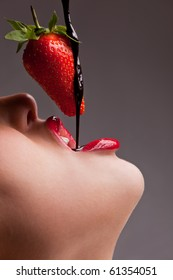 Beautiful girl eating a fresh red strawberry with chocolate sauce