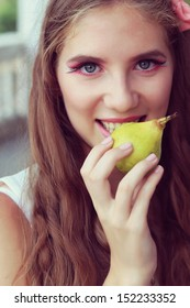 beautiful girl eating a pear. fashion portrait outdoors.
