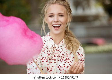 Beautiful girl eating pink cotton candy in the Park. Young woman walking and enjoying sweets outdoor.