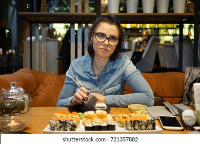 beautiful girl eating sushi in cafe