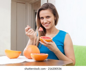 beautiful girl eats grapefruit with spoon at home