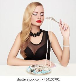 beautiful girl eats jewelry like a spaghetti.beauty fashion portrait of blond woman