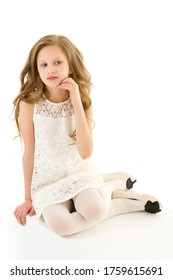 Beautiful Girl in Elegant Ivory Lace Dress Sitting on White Cube