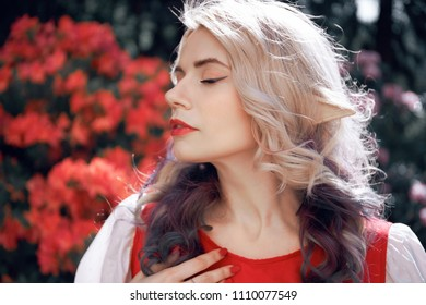 A beautiful girl with elven ears beauty portrait Fairy elf on the background of red flowers in a red dress. Red gentle shades