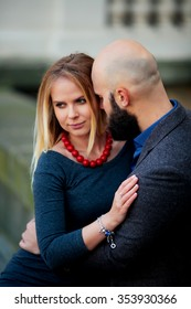 beautiful girl embraces the guy, stylishly dressed, bald man with a beard