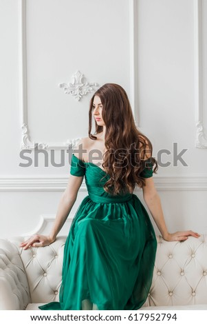 e1b23face49 beautiful girl in the emerald green dress brunette with long wavy hair on a  white background