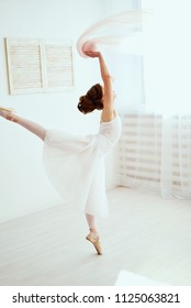 The beautiful girl is engaged in ballet in the training hall