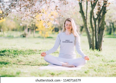 Beautiful girl engaged in yoga in a park near a flowering tree