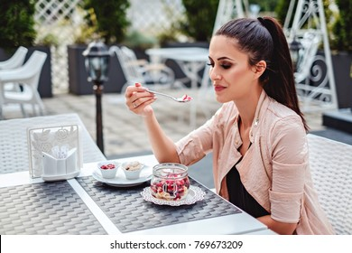 Beautiful girl enjoying fruit vanilla cake on the restaurant terrace