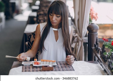 beautiful girl enjoying sushi in a cafe on a sunny day