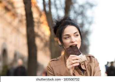 beautiful girl enjoys eating chocolate