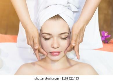 beautiful girl enjoys face massage in spa salon. Procedures for beauty and rejuvenation. Thai massage