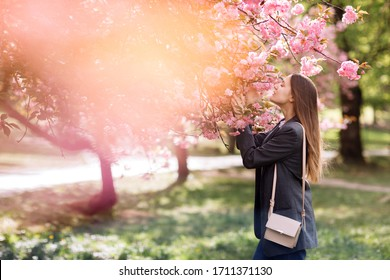 beautiful girl enjoys the scent of flowering tree. Portrait of beautiful woman with blooming cherry tree - girl inhales the scent of flowers with closed eyes - spring, nature and beauty concept.