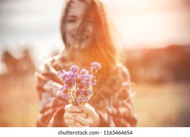 A beautiful girl enjoys the smell of a bouquet of cornflowers. Warm ethnic plaid, sunset. Beautiful red-haired young lady with freckles