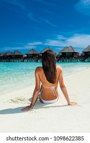 Beautiful girl enjoys a sunny beach on Olhuveli island in Maldives.