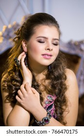 Beautiful girl in evening luxury dress celebrates Christmas in decorated christmas interior. Magical Christmas night.