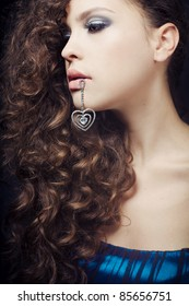 beautiful girl with evening makeup keeps the jewelry in her lips