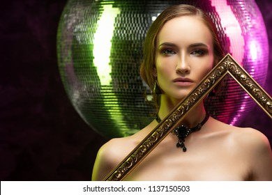 Beautiful girl with evening make-up wearing an elegant necklace and earrings of black opal holds an art frame in her hands at a mirror disco ball, illuminated by green and pink lights. Healthy skin.
