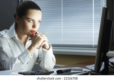 beautiful girl in the evening sits at office