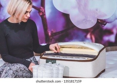 Beautiful girl examines the filler for the mattress. Coconut coir, Nature para latex rubber, memory foam independent spring.