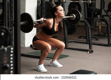 Beautiful girl exercising squatting with barbell