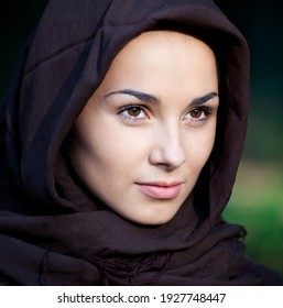 Beautiful girl face with head covering. Religious young woman. Girl's prayer outside. Nun. Holy sister.