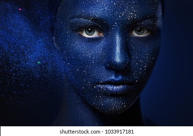 beautiful girl face painted with blue paint with glitter. The effect of the destruction. flying powder particles