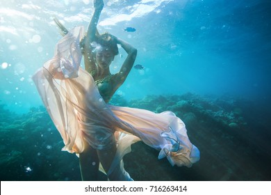 Beautiful girl in fashion dress posing underwater on coral reef on water background