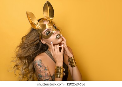 Beautiful girl in a fashionable golden leather mask of a rabbit on a yellow background. Concept for Halloween party