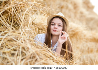 beautiful girl in a fashionable hat lying on a haystack on the farm in summer Sunny day