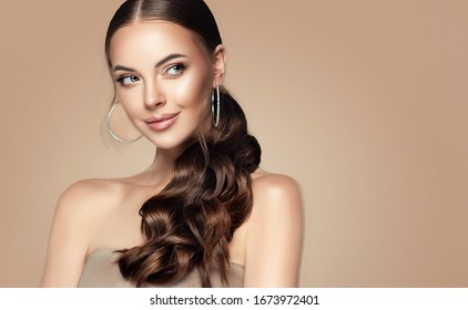 Beautiful girl . Fashionable and stylish woman in trendy jewelry big earrings .Curly ponytail hairstyle.  Fashion look  , beauty and style. Natural makeup and cosmetics