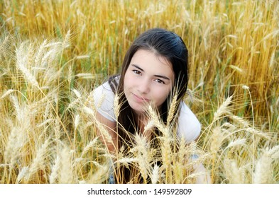 Beautiful girl in a field on a background of yellow and white wheat ears