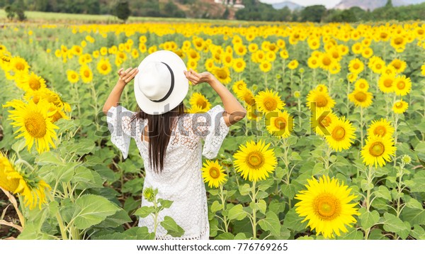 Beautiful girl in field of sunflowers, so happy and relax,