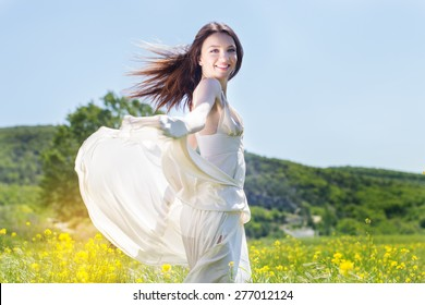Beautiful girl in the field of yellow flowers is wearing flying white wedding dress