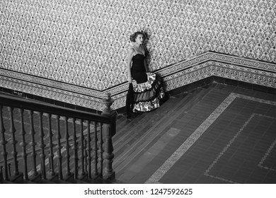 the beautiful girl in the flamenco dress goes up the stairs of a beautiful building with Andalusian style