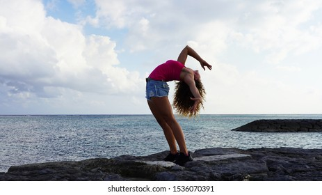a beautiful girl with flexible back stands on the seashore against a blue sky and clouds in rays of the setting sun. young curly model in bridge pose. life style gymnast clothing in backband position