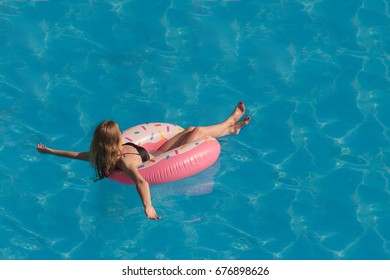A beautiful girl is floating on an inflatable circle in the pool