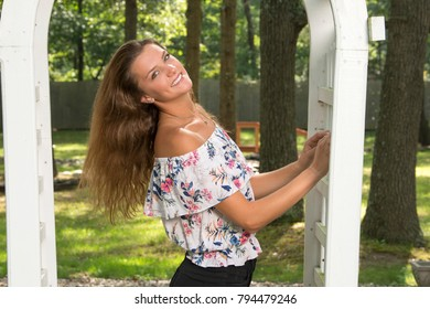 Beautiful girl in floral shirt and shorts stands in garden of home