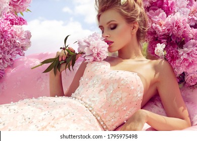 Beautiful girl in the flower garden in sofa