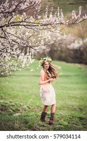 Beautiful girl in flowers crown playing with a wind under cherry tree