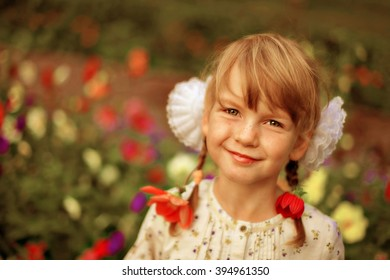 Beautiful girl with flowers in her hair smiling and looking at the camera