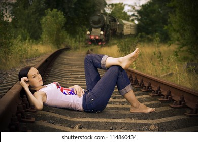 beautiful girl with flowers lying on the tracks before the train