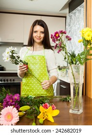Beautiful girl with flowers on  kitchen table