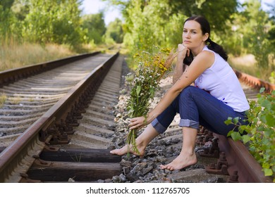 beautiful girl with flowers sitting on the rails